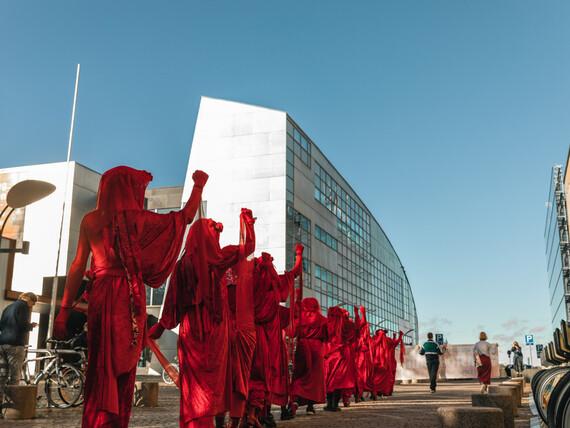 Valokuva. Puna-asuisia ihmisiä kävelee jonossa kaupunkimaisemassa. He ovat selin meihin, ja heillä on kaikilla oikean käden nyrkki pystyssä.