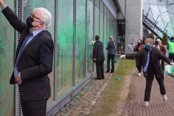 Ulkotila, suuria ikkunoita, joille on levitetty vihreää maalia. Joukko businessasuisia ihmisiä pyyhkii ikkunoita.